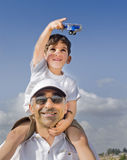 Boy on father shoulders with toy airplane. Boy on father shoulders with a toy airplane Stock Images
