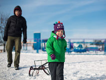 Boy and father sledging in winter park Stock Image