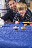 Boy with father spinning dreidel Stock Image