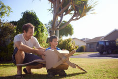 Boy father toy aeroplane. Son and dad playing with toy aeroplane in the garden at home having fun together and smiling Stock Image