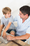 Boy and father using laptop. High angle view of boy and father using laptop at home stock image