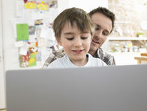 Boy And Father Using Laptop At Home. Little boy and father using laptop together at home royalty free stock photography