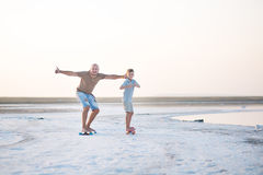A boy with father walks along the shore of the lake on skate board. A Salt lake shore. A Salt Lake. A boy with father walks along the shore of the lake on skate royalty free stock photography