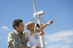 Boy With Father At Wind Farm. Little boy looking through binoculars with father at wind farm royalty free stock photos