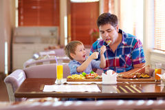 Boy feeding father in restaurant Stock Photo