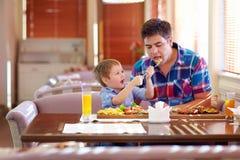 Boy feeding father in restaurant Stock Photo