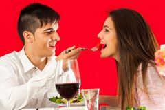 Boy feeding girlfriend at dinner table. Stock Images