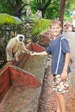 Boy feeds monkey Royalty Free Stock Images