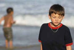 Boy Feeling Sad at the Beach. A young boy, nine years old, looks sad as another boy plays in the background at the beach Stock Photography