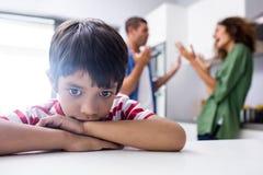 Boy feeling sad while his parents quarrelling. In kitchen Stock Photo