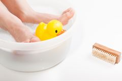 Boy feet in food bath with rubber duck Royalty Free Stock Images