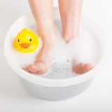 Boy feet in food bath with rubber duck Royalty Free Stock Image