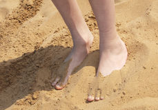 Boy with feet partly buried in sand Stock Photo
