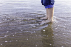 Boy feet standing water beach Royalty Free Stock Image