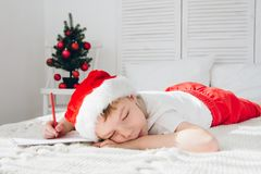 Boy fell asleep writing letters to Santa Stock Image