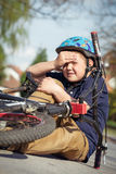 Boy fell from the bike in a park Royalty Free Stock Images