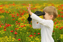Boy in a field with binoculars. Blond boy in a white shirt on a poppy field with binoculars in hand Royalty Free Stock Photos