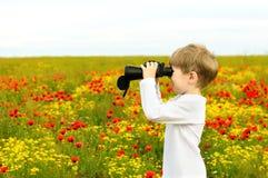 Boy in a field with binoculars. Blond boy in a white shirt on a poppy field with binoculars in hand Stock Photos