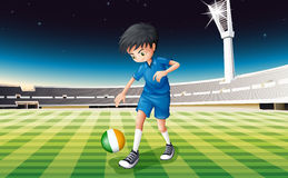 A boy at the field using the ball with the flag of Ireland Royalty Free Stock Image