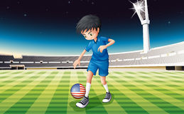 A boy at the field using the ball with the flag of the United St Stock Image