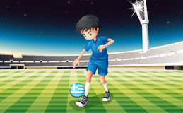 A boy at the field using the ball from Greece Royalty Free Stock Image