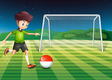 A boy at the field using the ball with the Singaporean flag Royalty Free Stock Photography