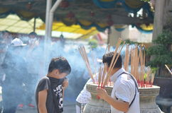 The boy fight for dad. Father and son at the Chinese Temple and the boy can't breath because of incense smoke Royalty Free Stock Photography