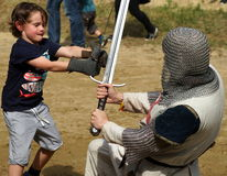 Boy Fighting Knight in Armor Royalty Free Stock Image