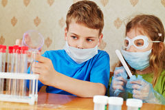 Boy fills chemical test tubes with specimen and girl watches after him Stock Image