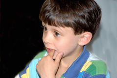 Boy with Finger in Mouth. A cute brown haired, brown eyed boy looking out with his finger in his mouth Royalty Free Stock Photo
