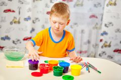 Boy finger paints on paper Stock Photography