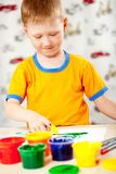 Boy finger paints on paper Royalty Free Stock Photos