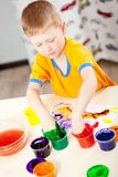 Boy finger paints on paper Stock Photos