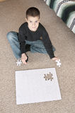 Boy finishing puzzle Royalty Free Stock Photo