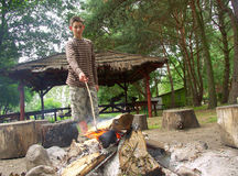 Boy by the fire. A boy standing by the camp-fire in a forest campingsite Royalty Free Stock Photography