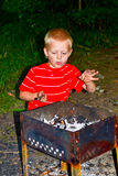 A boy and a fire. Boy kindles a fire in the garden stock photos