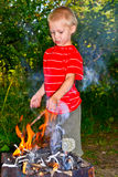 A boy and a fire. Boy kindles a fire in the garden Royalty Free Stock Photos
