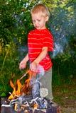 A boy and a fire. Boy kindles a fire in the garden royalty free stock photos