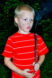 A boy and a fire. Boy kindles a fire in the garden stock photo