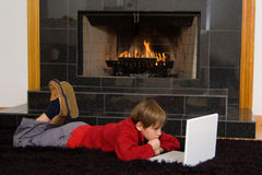 Boy at Fireplace on Computer. Boy with laptop in front of fireplace royalty free stock photography