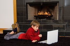 Boy at Fireplace on Computer. Boy with laptop in front of fireplace royalty free stock images