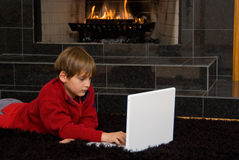 Boy at Fireplace on Computer. Boy with laptop in front of fireplace royalty free stock photo