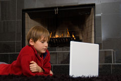 Boy at Fireplace on Computer. Boy with laptop in front of fireplace stock image