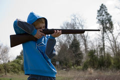 Boy firing rifle Stock Image
