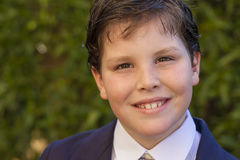 Boy first communion dress smiling to the camera. Color portrait of ten year old boy dressed in dark blue suit and tie for his first communion with green leaves Royalty Free Stock Image