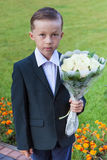 Boy first-grader with bouquet Royalty Free Stock Image