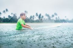 Boy first step surfer learning to surf under the rain Royalty Free Stock Photo