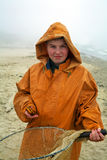Boy with fisherman's coat. Young amber cather - fisherman smiling standing  by the sea with fisherman's coat on misty day Royalty Free Stock Photos