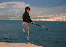 Boy fishes in the sea Stock Photography