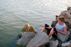 Boy fishing. The boy on stones in sea of Azov fishes Stock Photo